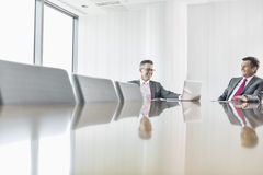Smiling businessmen talking in conference room Royalty Free Stock Photo
