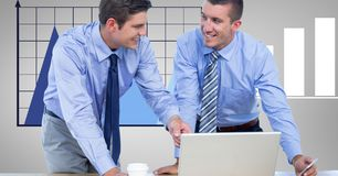 Smiling businessmen using laptop against graph stock images