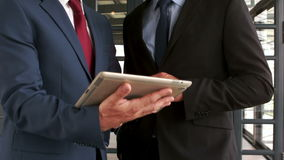 Smiling businessmen using tablet. In the office stock video footage