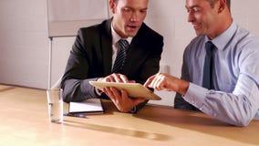 Smiling businessmen using tablet stock video