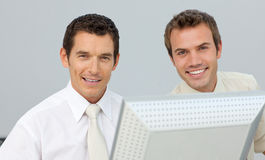 Smiling businessmen working together at a computer Royalty Free Stock Photos