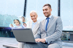 Smiling businesspeople with laptop outdoors. Business, communication, technology and people concept - smiling businesspeople making video call or conference with Royalty Free Stock Images