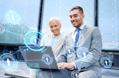 Smiling businesspeople with laptop outdoors Stock Image