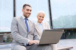 Smiling businesspeople with laptop outdoors Royalty Free Stock Photos