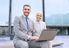 Smiling businesspeople with laptop outdoors Royalty Free Stock Image
