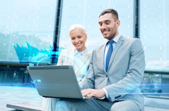Smiling businesspeople with laptop outdoors Stock Images