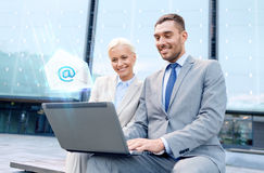Smiling businesspeople with laptop sending e-mail. Business, technology, communication and people concept - smiling businesspeople sending e-mail with laptop Royalty Free Stock Photo