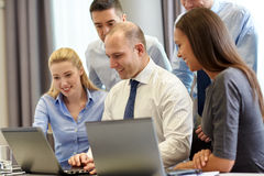 Smiling businesspeople with laptops in office Stock Photo