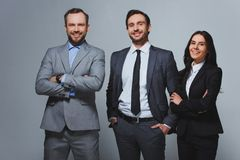 Smiling businesspeople looking at camera. On grey royalty free stock photography