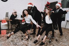 Smiling Businesspeople on New Year Party in Office. New Year Eve. Smiling Businessman. Man in Santa Claus Cap. Celebrating of New Year. Modern Office. People royalty free stock photos