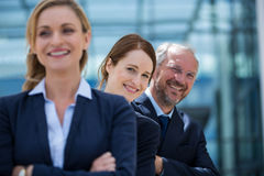 Smiling businesspeople standing with hands crossed. In office premises Royalty Free Stock Image