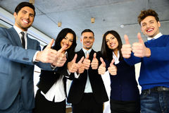Smiling businesspeople standing with thumbs up Royalty Free Stock Photography