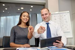 Smiling businesspeople with tablet pc in office Stock Images