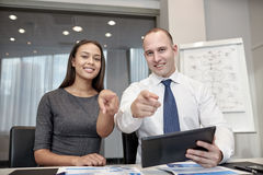 Smiling businesspeople with tablet pc in office Royalty Free Stock Images