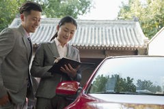 Smiling Businesspeople Working Outdoors By Red Car Stock Photography