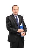 Smiling businessperson holding a folder. A smiling businessperson holding a folder with documents isolated against white background Stock Images