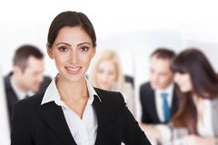 Smiling businesswoman against team discussing in boardroom Royalty Free Stock Photos