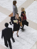 Smiling Businesswoman Amid Blurred Walking People Royalty Free Stock Image