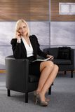 Smiling businesswoman in armchair Royalty Free Stock Photo