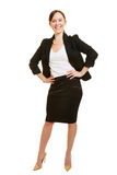 Smiling businesswoman with arms akimbo Stock Images
