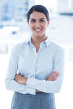 Smiling businesswoman with arms crossed at office Stock Photography