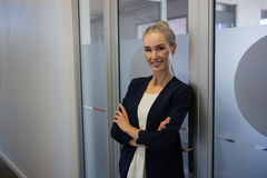 Smiling businesswoman with arms crossed standing by door at office Royalty Free Stock Photography