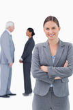 Smiling businesswoman with arms folded and colleagues behind her Stock Photography