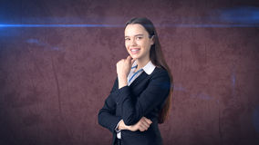 Smiling businesswoman with arms folded looking at you. Standing over brown background. Stock Images