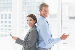 Smiling businesswoman back-to-back with colleague Stock Photo