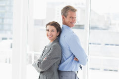 Smiling businesswoman back-to-back with colleague Royalty Free Stock Photo