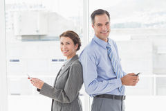 Smiling businesswoman back-to-back with colleague Stock Images