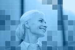 Smiling businesswoman behind monochrome blue grid Royalty Free Stock Image