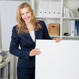 Smiling Businesswoman With Billboard In Office Stock Photography
