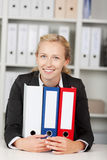 Smiling Businesswoman With Binders Sitting At Desk Stock Photos