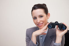 Smiling businesswoman with binoculars Stock Photo
