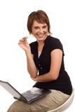 Smiling businesswoman biting her spectacles. Smiling Caucasian businesswoman sitting on chair working on laptop while biting her spectacles' temple Stock Image