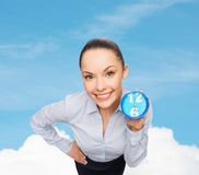 Smiling businesswoman with blue clock. Business, time and deadline concept - smiling businesswoman with blue clock Royalty Free Stock Images