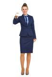 Smiling businesswoman in blue suit holding up business card. A happy business woman in a blue skirt-suit smiles as she holds up her business card Royalty Free Stock Photos