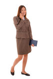 Smiling businesswoman in brown suit is using smartphone and hold Stock Image