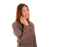Smiling businesswoman in brown suit is using smartphone on white Royalty Free Stock Photo