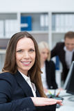 Smiling businesswoman in a busy office Royalty Free Stock Images