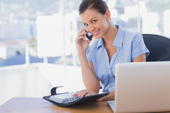 Smiling businesswoman calling with her mobile phone. In the office Royalty Free Stock Image