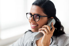 Smiling businesswoman calling on phone at office Stock Photos