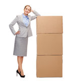 Smiling businesswoman with cardboard boxes stock image