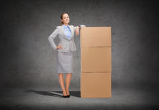 Smiling businesswoman with cardboard boxes Royalty Free Stock Images