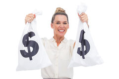 Smiling businesswoman carrying cash bags Stock Photo