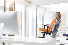 Smiling businesswoman carrying orange chair in new office stock images