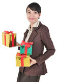 Smiling businesswoman carrying pile of gifts Stock Photo