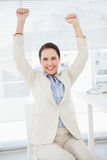 Smiling businesswoman celebrating at work Royalty Free Stock Images