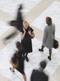 Smiling Businesswoman With Cellphone Amid Blurred Walking People Stock Images